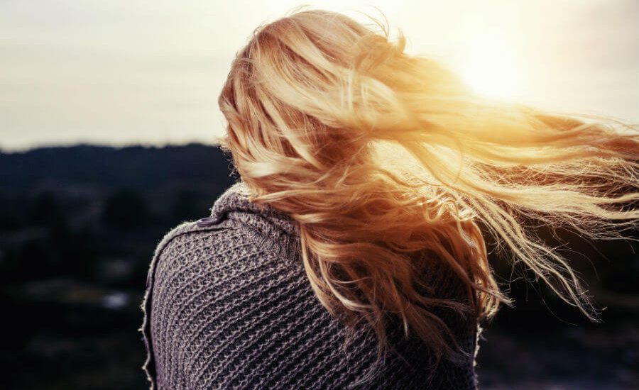 blonde hair woman looking at sunset